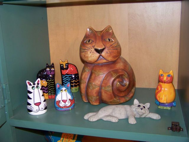 Multiple cat figurines in hutch